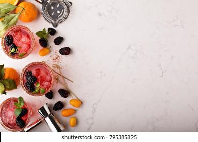Blackberry citrus margaritas with bartender tools overhead shot