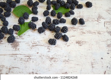 Blackberry closeup on rustic vintage wooden white table. Blackberries with green leaves on white shabby surface.