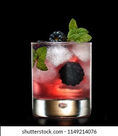 blackberry cocktail isolated on a black background decorated with mint