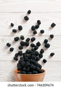Blackberry explosion. Photo of blackberry in clay bowl on white wooden table. Top view. High resolution product.