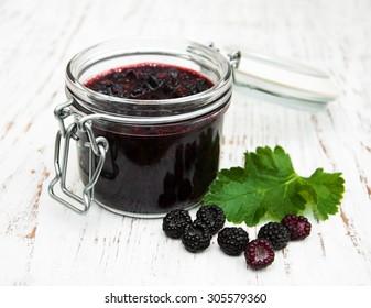Blackberry jam and fresh blackberries on a wooden background