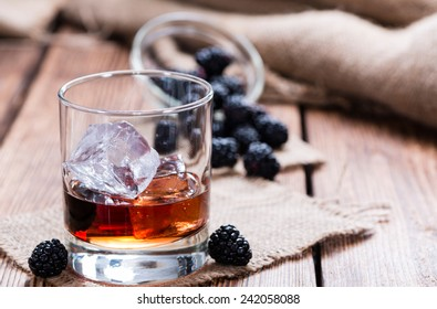 Blackberry Liqueur in a shot glass (on rustic wooden background)