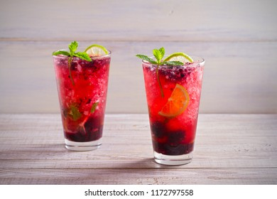 Blackberry mojito cocktail with berries, lime and mint on wooden background. horizontal