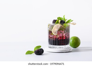 Blackberry mojito cocktail with lime on neutral light background. Summer freshness beverage for festive party. Holiday mocktail with copy space.