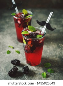 Blackberry mojito with mint, ice and frozen berries.