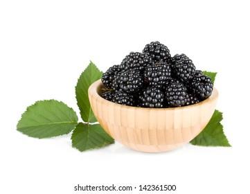 Blackberry in wooden bowl. Isolated on white background