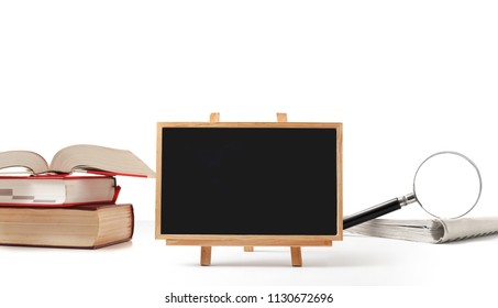 blackboard and books with magnifying glass on white background