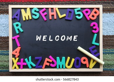 Blackboard with chalk, colorful alphabet and text welcome.