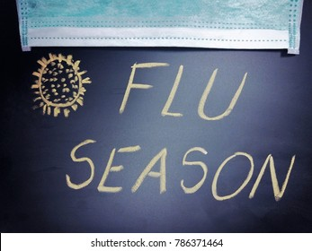 Blackboard or chalkboard with the phrase Flu season written on it and drawn influenza viruses and a medical face mask, flu season concept