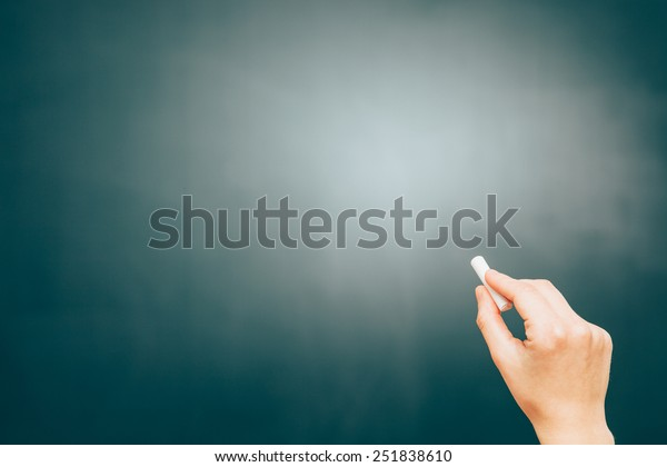 Blackboard with copy space and a hand with a chalk.