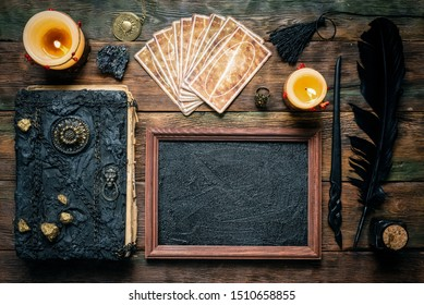Blackboard with a copy space, tarot cards, magic book and magical wand on the wooden table background. School of magic concept.