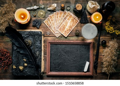 Blackboard with a copy space, tarot cards, crystal ball, magic book and magical wand on the wooden table background. School of magic concept.