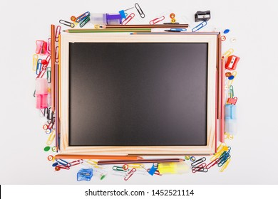 Blackboard with different school stationery