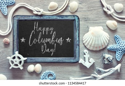 """Blackboard  with frame made of sea shells, stones, rope and star fish on light textured background, text """"Happy Columbus Day"""""""