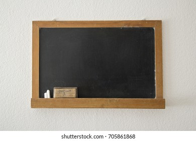 Blackboard hanging on a wall with chalk and eraser left. Back to school. Chalkboard.