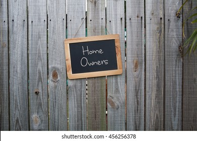 Blackboard home owners sign on wooden fence