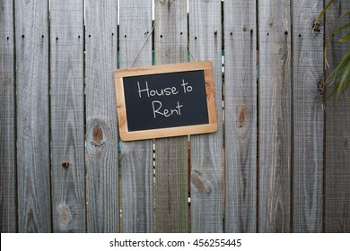 Blackboard house to rent sign on wooden fence