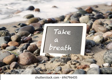 blackboard lying between stones on sandy beach with the words Take A Breath