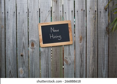 Blackboard Now Hiring sign on wooden fence