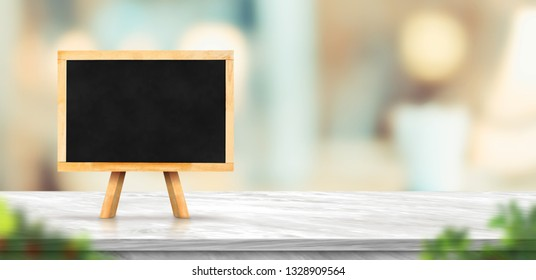 Blackboard on white marble table and blurred soft light table in luxury restaurant with bokeh background. product display template.Business presentation