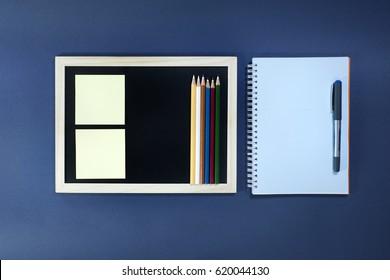 Blackboard with pencils, notebook