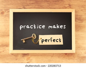 blackboard with the phrase practice makes perfect written on it over wooden background