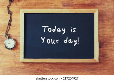 blackboard with the phrase today is your day written on it next to old clock over wooden table