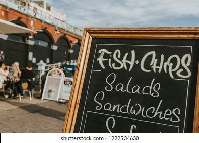 Blackboard with restaurant menus and information in the middle of a promenade, with Fish and Chips, salads, sandwiches and other food.
