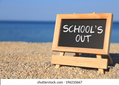Blackboard with School's out text on the beach, Holiday sign