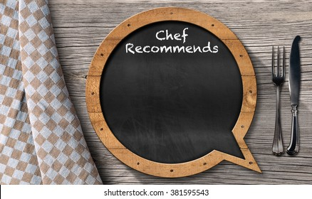 Blackboard in the shape of speech bubble with text Chef Recommends and silver cutlery on a wooden table with a checkered tablecloth