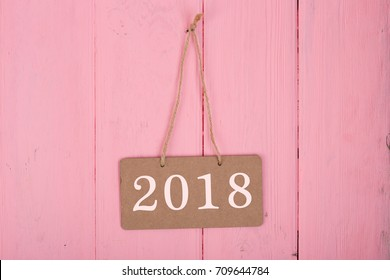 "Blackboard with text ""2018"" on pink wooden background"