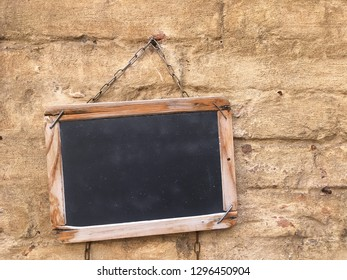 Blackboard with wooden frame on old wall.
