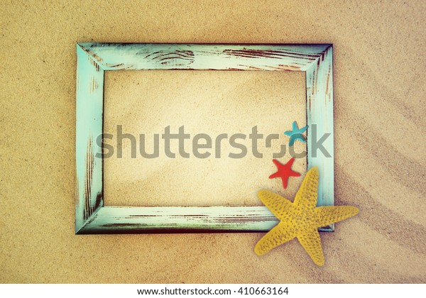 Blackboard with wooden frame and shells on the sand.