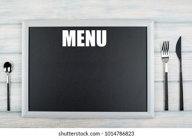 Blackboard with the word Menu written on it, among covered kitchen on wooden table. Menu. Food