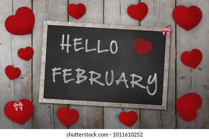 Blackboard with words hello february, surrounded by red hearts, on vintage wooden background