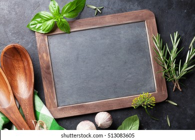 Blackboard for your text, fresh garden herbs and spices on stone table. Basil, rosemary, dill. Cooking ingredients. Top view with copy space