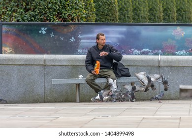Blackburn, Lancashire/England - 22.05.2019 - Man sat on bench feeding pigeons