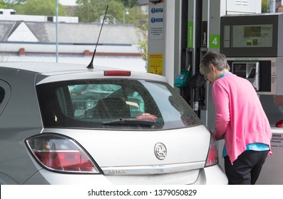 Blackburn, Lancashire/UK - April 23rd 2019: Elderly Caucasian woman with grey hair putting petrol in her car at Asda petrol station