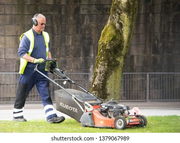 Blackburn, Lancashire/UK - April 23rd 2019: Blackburn with Darwen Council male worker wearing high visibility vest mowing the grass