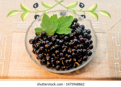 Blackcurrant berries with leaves, blackcurrant in a bowl