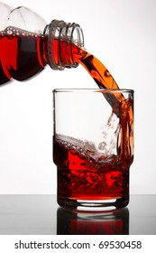 blackcurrant juice pouring into glass, close up on white background