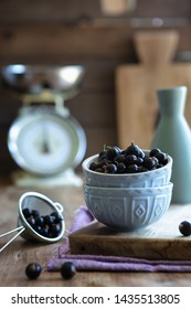 Blackcurrants piled up in pale blue bowls with a sieve of blackcurrants in a rustic kitchen portrait