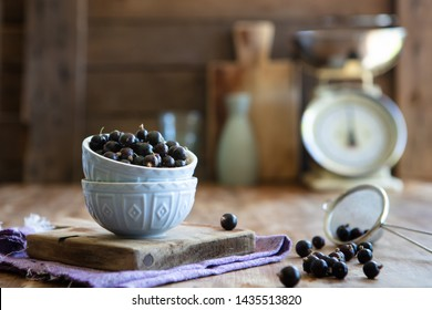Blackcurrants piled up in pale blue bowls with a sieve of blackcurrants in a rustic kitchen