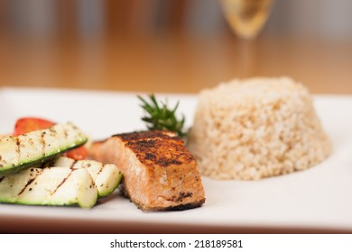 Blackened salmon with brown rice and grilled zucchini and tomatoes