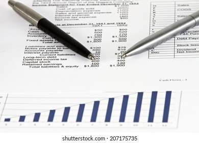 Black&Gold&Silver pens showing financial report