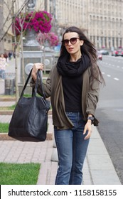 A black-haired girl in jeans with sunglasses in the city on the background of the avenue, passers-by, in a big black scarf, jacket, big bag, street fashion