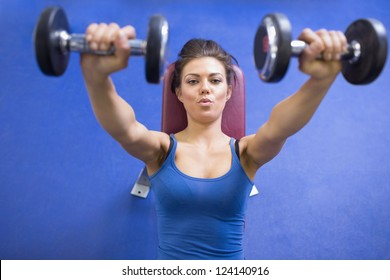 Black-haired woman energetically lifting weights