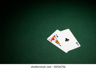 Blackjack hand on green baize table ace and king