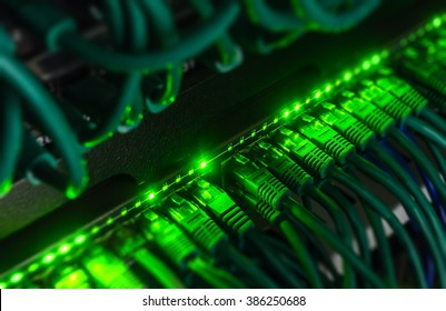 Blackout, blurred borders. Close up of green network cables connected to black switch glowing in the dark