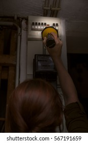 Blackout, electricity cut, woman with flashlight checking the breaker box, fuse box